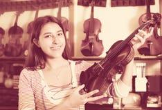 Muchacha que elige el violín en tienda de la música Foto de archivo