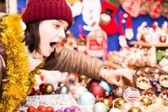 Muchacha que elige la decoración de la Navidad en el mercado Foto de archivo