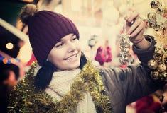 Muchacha que elige la decoración de la Navidad en el mercado Fotos de archivo
