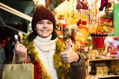Muchacha que elige la decoración de la Navidad en el mercado Fotografía de archivo libre de regalías