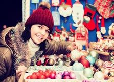 Muchacha que elige la decoración de la Navidad en el mercado Fotografía de archivo