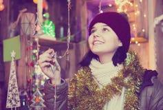 Muchacha que elige la decoración de la Navidad en el mercado Imagen de archivo