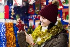 Muchacha que elige la decoración de la Navidad en el mercado Imagen de archivo libre de regalías