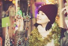 Muchacha que elige la decoración de la Navidad en el mercado Imagenes de archivo