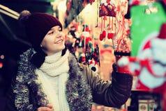 Muchacha que elige la decoración de la Navidad en el mercado Fotos de archivo libres de regalías