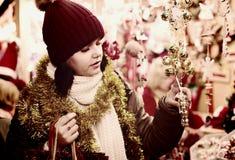 Muchacha que elige la decoración de la Navidad en el mercado Imágenes de archivo libres de regalías