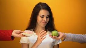 Muchacha que elige la manzana en vez del buñuelo, del azúcar natural y de la vitamina contra la confitería almacen de metraje de vídeo