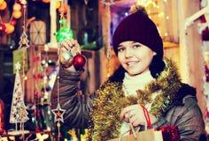 Muchacha que elige los regalos en la feria festiva antes de la Navidad Fotos de archivo