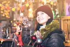 Muchacha que elige los regalos en la feria festiva antes de Navidad Foto de archivo libre de regalías