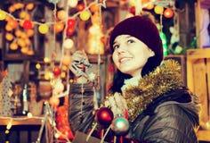 Muchacha que elige los regalos en la feria festiva antes de Navidad Imágenes de archivo libres de regalías