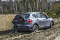 Muchacha que empuja el coche pegado en el camino de tierra del pantano imagen de archivo