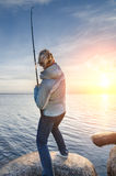 Muchacha que engancha un pescado en la orilla del lago Imágenes de archivo libres de regalías
