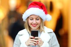 Muchacha que envía mensajes de teléfono en días de fiesta de la Navidad Imagen de archivo libre de regalías