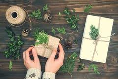 Muchacha que envuelve el regalo de la Navidad Las manos de la mujer que sostienen la caja de regalo adornada en la tabla de mader Foto de archivo libre de regalías