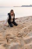 Muchacha que escribe Año Nuevo en arena Foto de archivo
