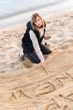 Muchacha que escribe Año Nuevo en arena Imagen de archivo libre de regalías