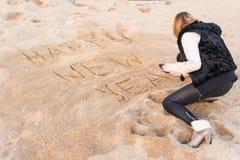 Muchacha que escribe Año Nuevo en arena Imagenes de archivo