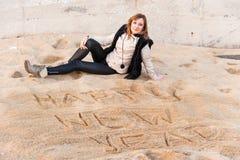Muchacha que escribe Año Nuevo en arena Fotos de archivo