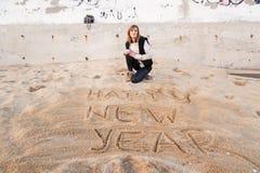 Muchacha que escribe Año Nuevo en arena Foto de archivo libre de regalías