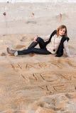Muchacha que escribe Año Nuevo en arena Fotos de archivo libres de regalías