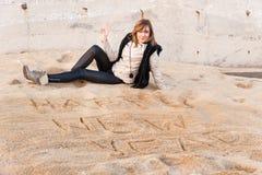Muchacha que escribe Año Nuevo en arena Fotografía de archivo libre de regalías