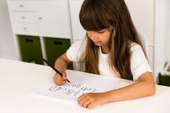 Muchacha que escribe el alfabeto de ABC Imagenes de archivo