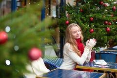 Muchacha que escribe las postales de Christma en café parisiense Imágenes de archivo libres de regalías