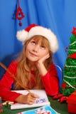 Muchacha que escribe una letra a santa Imágenes de archivo libres de regalías