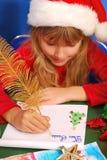 Muchacha que escribe una letra a santa Fotos de archivo