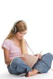 Muchacha que escucha el libro de la música y de lectura Fotos de archivo