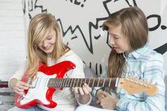 Muchacha que escucha la hermana que toca la guitarra eléctrica en casa Fotografía de archivo libre de regalías