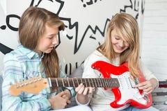 Muchacha que escucha la hermana que toca la guitarra eléctrica en casa Imagen de archivo