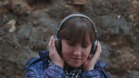 Muchacha que escucha la música con los auriculares almacen de video