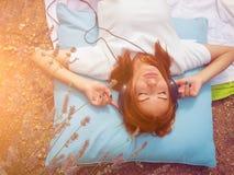 Muchacha que escucha la música con los auriculares Imagen de archivo libre de regalías