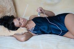 Muchacha que escucha la música con los auriculares imagenes de archivo