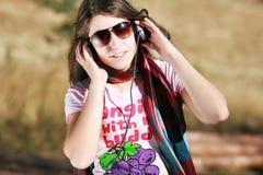 Muchacha que escucha la música con los auriculares Fotografía de archivo