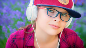 Muchacha que escucha la música con los auriculares al aire libre Foto de archivo