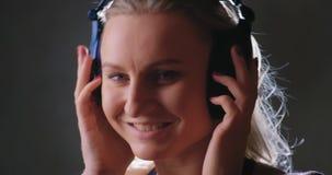 Muchacha que escucha la música con los auriculares metrajes