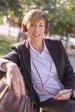Muchacha que escucha la música con los auriculares en un parque Imágenes de archivo libres de regalías
