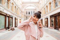 Muchacha que escucha la música con los auriculares en una calle de la ciudad Imagen de archivo libre de regalías