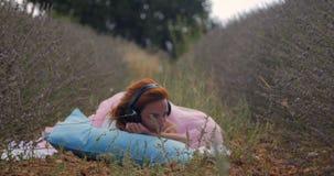 Muchacha que escucha la música con los auriculares en verano almacen de video