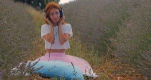 Muchacha que escucha la música con los auriculares en verano metrajes