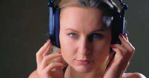 Muchacha que escucha la música con los auriculares almacen de metraje de vídeo