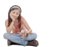 Muchacha que escucha la música con su smartphone, CRO (coordinadora) que se sienta del preadolescente Fotografía de archivo libre de regalías