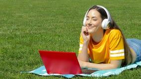 Muchacha que escucha la música con un ordenador portátil y los auriculares metrajes
