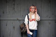 Muchacha que escucha la música, muchacha que disfruta de música, relajándose, auriculares anaranjados, lanzamiento de la calle, e Fotos de archivo libres de regalías