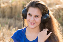Muchacha que escucha la música en campo Imagenes de archivo