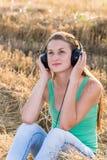 Muchacha que escucha la música en campo Fotografía de archivo