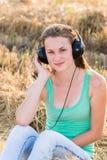 Muchacha que escucha la música en campo Foto de archivo libre de regalías