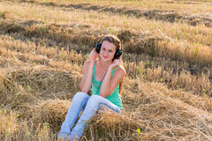 Muchacha que escucha la música en campo Imagen de archivo libre de regalías